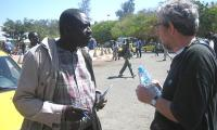 Aliou Sall discusses with a participant from Canada at the WSF 2011